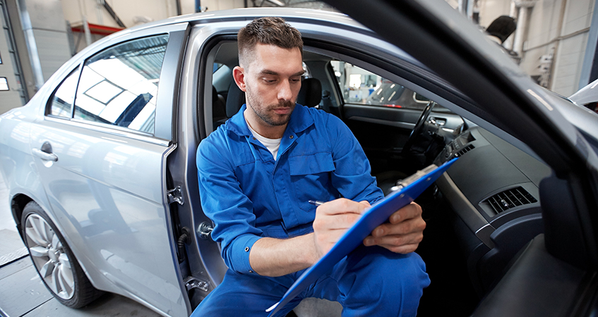 Technician in car with checklist on clipboard - MOT Testing Penrith