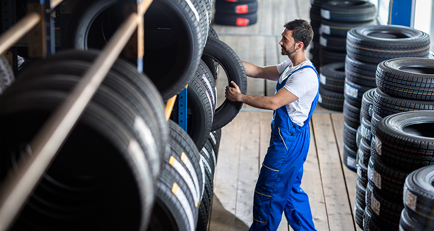 Technician choosing tyre from wide range on rack - Tyres Penrith